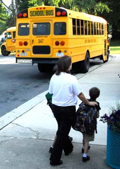 Adult and child walking toward school bus