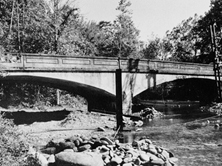 No-longer-extant three-span Oconaluftee Bridge over Oconaluftee River, Cherokee, Swain County: constructed by Luten Bridge Company in 1921 (source: Library of Congress, Prints & Photographs Division, HAER, Reproduction number HAER NC-40-2)