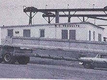Prestressed concrete girder leaving Durham plant on specially designed trailer truck for bridge under construction over Cape Fear River in Elizabethtown (Bladen County Bridge 17) in 1957 (source: North Carolina Roadways, March-April 1957)